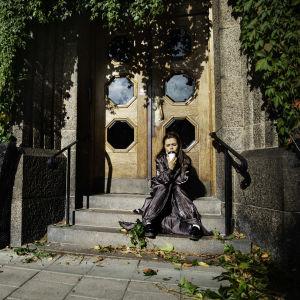 På bilden syns författaren och regissören Caroline Ringskog Ferrada-Noli. Hon sitter på en trappa iklädd en svart jacka och håller i en take away-kaffe.