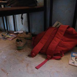 Punainen reppu ja kenkiä lattialla. Tavarat kuuluivat koulusta siepatuille lapsille.