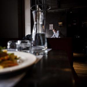En matportion, och i bakgrunden en servitör som jobbar på restaurang Vltava i Helsingfors i oktober 2020.