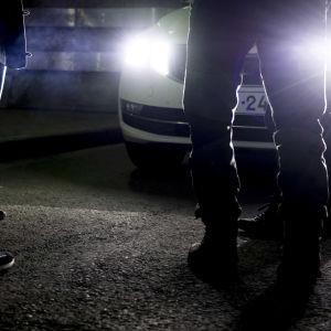 Människors fötter framför en bil i mörkret. Bilen har ljusen tända.