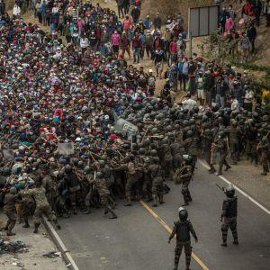 Guatemalanska soldater tog till käppar, batonger och tårgas för att tvinga tillbaka honduranska migranter vid en vägspärr i staden Chiquimuta på söndagen.