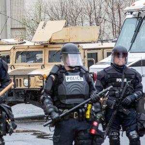 Kravallutrustad polis stod på vakt utanför polisstationen i Minneapolis-förorten Brooklyn Center på måndagen, efter dödsskjutningen där.