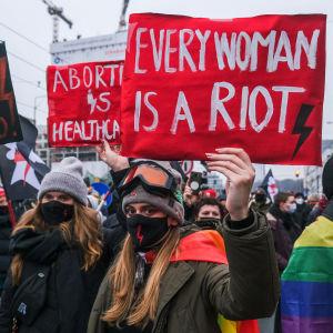 Aborttimielenosoitukseen osallistuvat naiset näyttävät kylttejä.