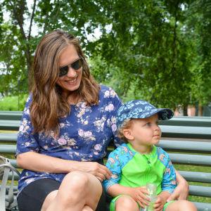 Emma Lavonen med sitt barn Aaron Lavonen på en bänk i en park.