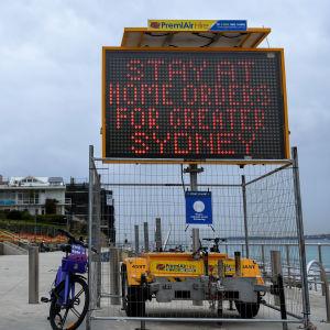 Bild på en vägskylt där det står att sydneyborna ska stanna hemma.