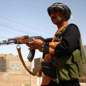 Två beväpnade afghanska milismän. I bakgrunden syns en mur och ett hus.