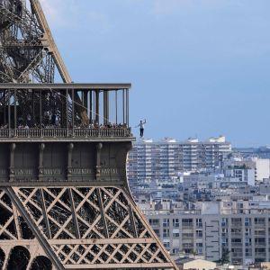 En lindansare balanserar i luften med Eiffeltornet bakom sig.
