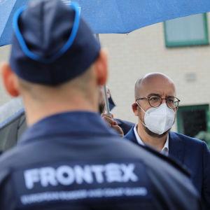 Bild på baksidan av en man i Frontex-uniform. Bakom honom står Europeiska rådets ordförande Charles Michel.