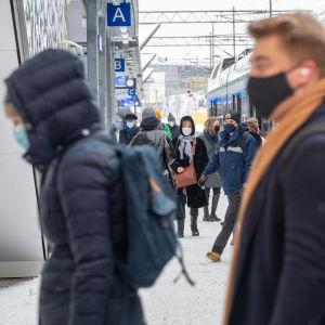 Tågpassagerare står på perrongen i Böle i Helsingfors.