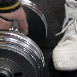 Träningssko och hantel i gym.