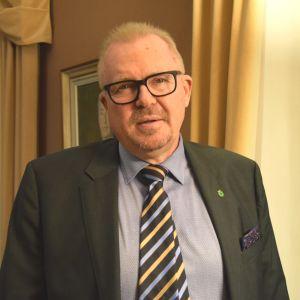 En bild på en man med glasögon som har kostym och slips. Han har även en liten brosch som föreställer Raseborgs stadsvapen. Mannen är Ragnar Lundqvist.