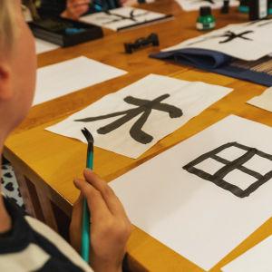 Pöydällä papereita, joissa japanilaisia kirjoitusmerkkejä, sivustalla näkyy lasta, jonka kädessä sivellin