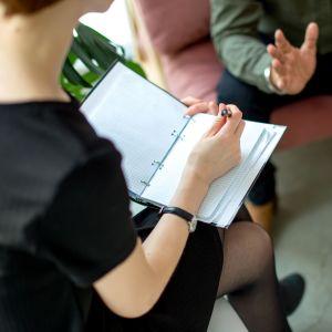 En psykolog sitter och pratar med en klient. Hon antecknar i ett block.