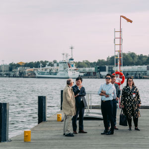 A group of people standing on a waterside dock.