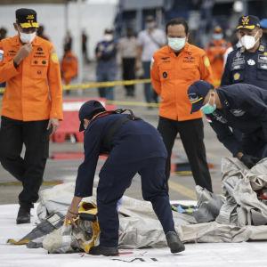 Poliser studerar innehållet i säckar på marken.