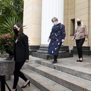 Regeringspartiernas orförande vandrar ner för en stentrappa på rad.