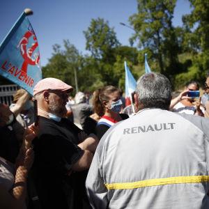 Personer står med ryggen mot kameran. De står utanför en Renaultfabrik i Frankike. På en persons jacka står det Renault.