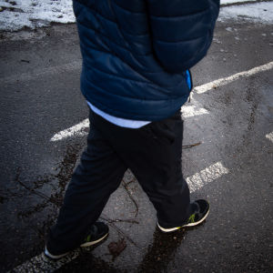 Ett barn går längs en våt väg, följer en vit pil målad på asfalten.
