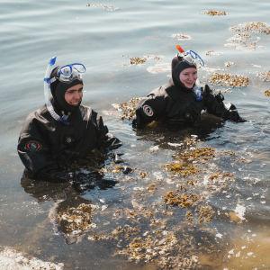 Kaksi lukiolaista rantavedessä kuivapuvut ja snorkkelit päällä Dalskär-saarella.