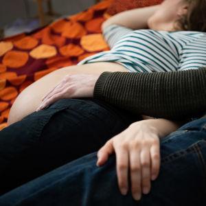 Mies pitää kättään odottavan naisen paljaalla vatsalla.