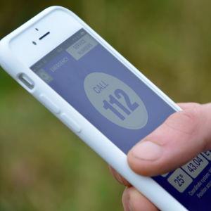 Bild på en telefon hållen i högerhand med nödcentralsapplikationen öppen.