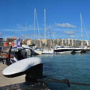 Lyxbåtar som ligger i hamn med blått hav i förgrunden.