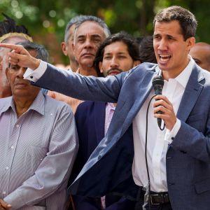 Juan Guaidó talar i mikrofon.