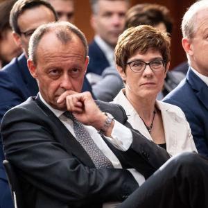 Friedrich Merz sitter brevid Annegret Kramp-Karrenbauer i en mötessal.