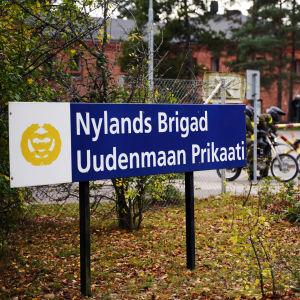 En skylt där det står Nylands brigad på svenska och finska. I bakgrunden syns porten till garnisonsområdet.