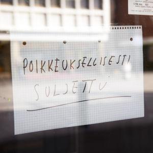 """En handskriven lapp i ett fönster där det står """"poikkeuksellisesti suljettu""""."""