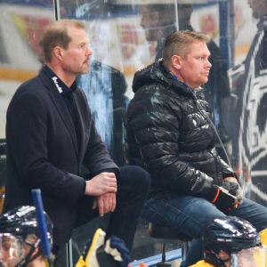 Pekka Virta lotsar Lukko från sin barstol i spelarbåset. Till vänster assisterande tränaren Erik Hämäläinen.