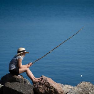 Tyttö onkii kivien päällä meren rannassa.