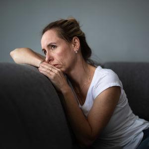 Ledsen kvinna sitter på en soffa och tittar ut.