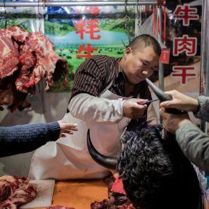 En slaktare säljer jakkött på en marknad i Peking, Kina.