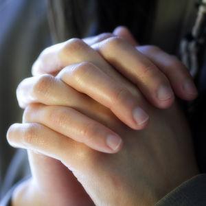 Närbild på två ihopknäppta händer.