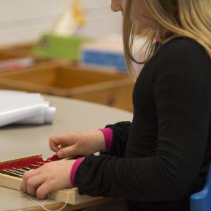 Flicka undervisas i textilslöjd