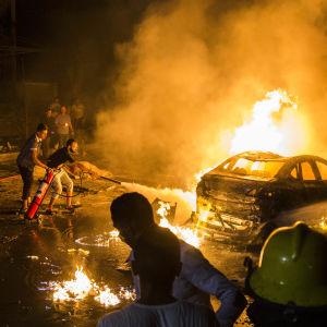 Personer försöker släcka eldsvådan efter en bilexplosion i Kairo.