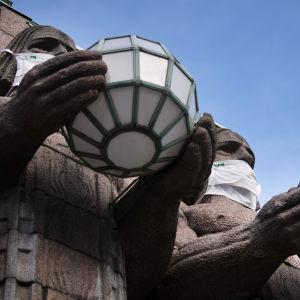 Munskyddsklädda statyer vid järnvägsstationen i Helsingfors.