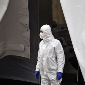 Person i vit skyddsutrustning står utanför öppningen till ett stort vitt tält.