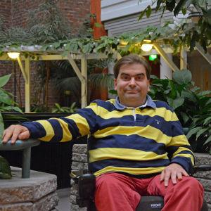 En man sitter inomhus i en rullstol framför en massa gröna växter och träd.