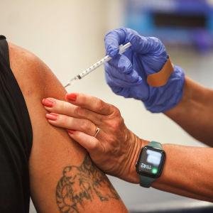Närbild av en arm. En sjukskötare sticker coronavaccin i armen.