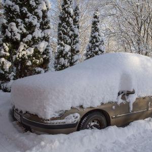 Talvisessa pihapiirissä parkkeerattu auto on hautatutunut lumikerroksen alle.