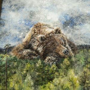 Villasta valmistettu taulu, jossa karhu nukkuu suolla.