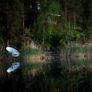 Ett fritidshus och en båt vid en sjö.