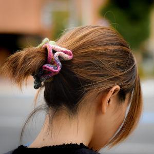 En kvinna med brunt hår uppsatt i ponnysvans med hårsnodd  fotograferat bakifrån så att ansiktet inte syns. (schrunchie)