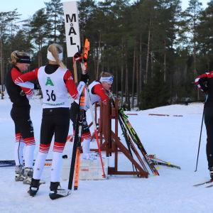 """En grupp flickor på skidor står runt en stolpe där det står """"mål""""."""