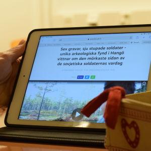 En läsplatta med en artikel som Yle Västnyland skrivit. Handlar om krigsarkeologiskt fynd i Hangö där man hittade sovjetiska soldatgravar.
