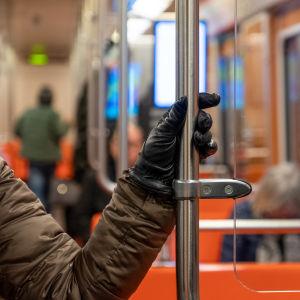 Käsi pitää kiinni metron kaiteesta