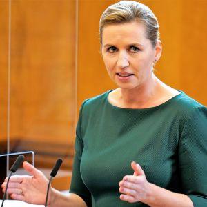 Tanskan pääministeri Mette Frederiksen puhuu parlamentissa tehostaen sanomaa samalla käsillään. Hänellä on vihreä asu.