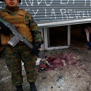 En soldat övervakar ett vandaliserat köpcenter i Santiago. Åtminstone 40 köpcenter och andra företag plundrades på söndagen, enligt det chilenska inrikesministeriet.